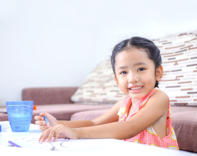Portrait Of Cute Girl Drawing At Table In Home