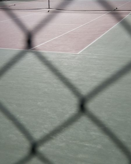 High angle view of tiled floor seen through chainlink fence