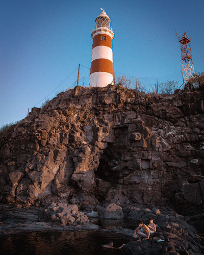 Low angle view of lighthouse on rock against sky