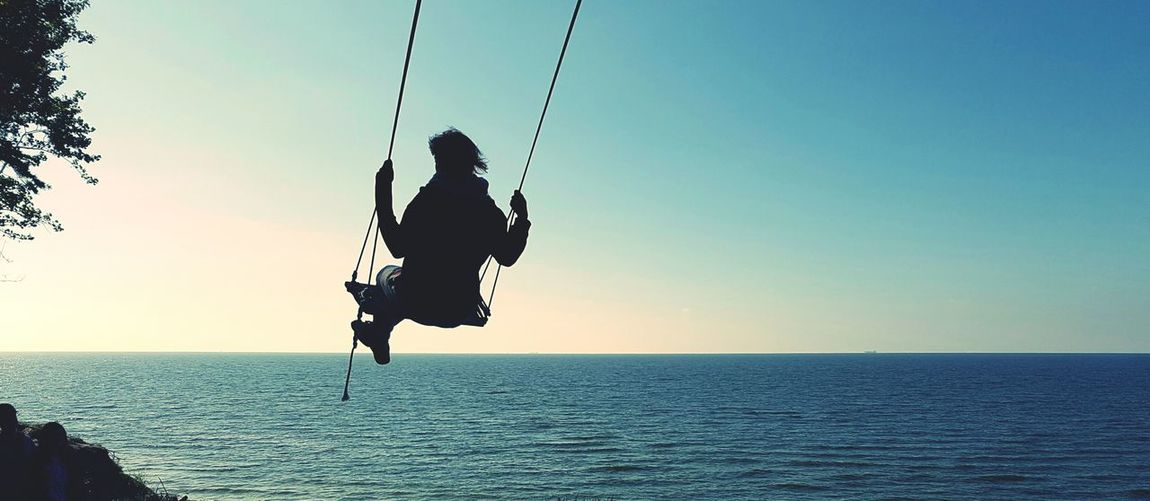 Full length of person swinging over sea against clear sky