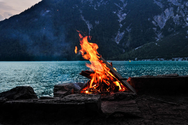 Bonfire against lake and mountain
