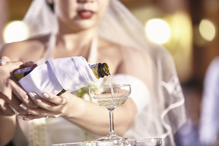 Close-up of bride pouring champagne