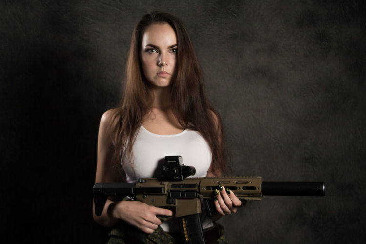 Adult Beautiful Woman Beauty Black Background Brown Hair Contemplation Front View Gun Hair Hairstyle Holding Indoors  Long Hair Looking At Camera One Person Portrait Standing Teenager Waist Up Weapon Young Adult Young Women