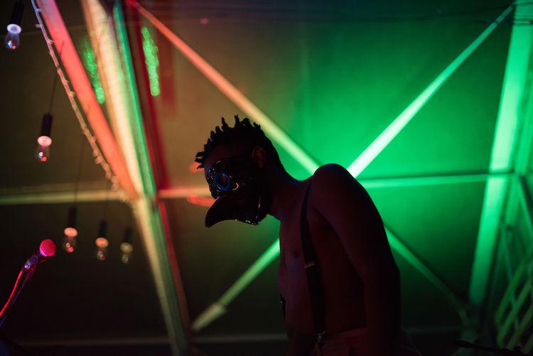 Low angle view of shirtless man wearing mask in nightclub