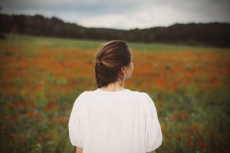 Rear view of woman standing on blooming poppy field