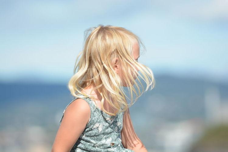 Girl looking at sea against sky
