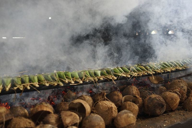 Food in wrapped leaves on barbecue grill