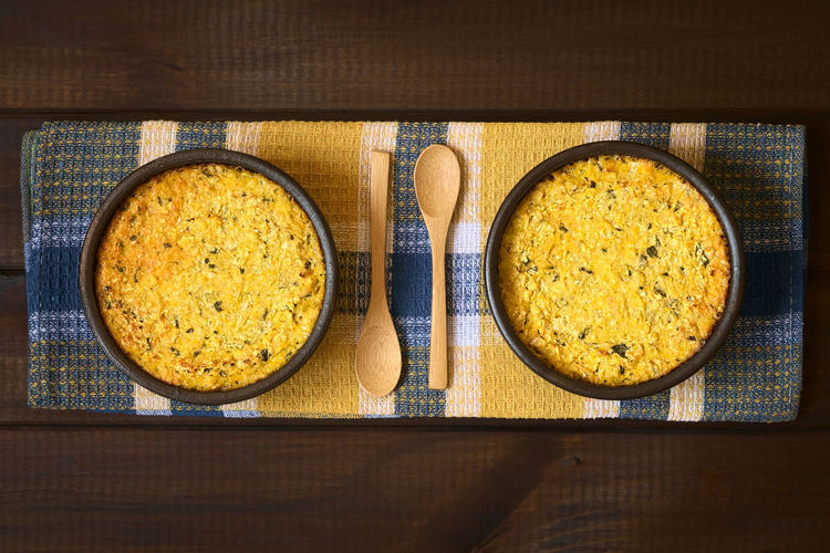 Traditional Chilean corn pie called Pastel de Choclo a baked dish made of corn-basil mix covering ground meat, olive, boiled egg, raisins and pieces of chicken. Photographed overhead on dark wood with natural light Chile Chilean  Choclo Dish Homemade Homemade Food Latin American Food  Meal Pastel De Choclo Rustic South American Food Baked Blended Chilean Food Corn Corn Pie Food Food And Drink Fresh Meal Overhead View Pastel Pie Traditional Vegetable