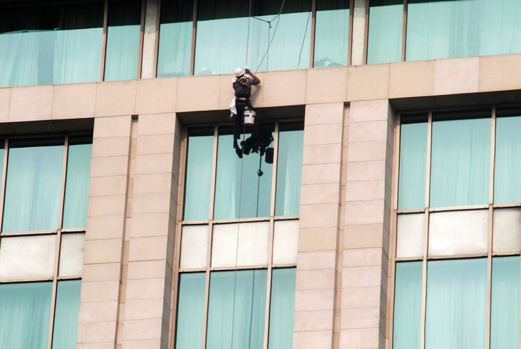 A worker cleaning window glass of a high rise building corporate office
