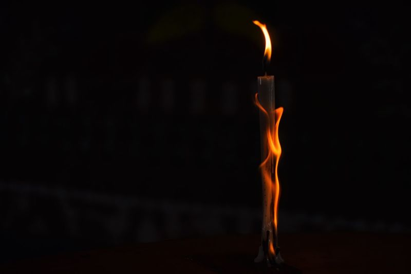 Close-up of burning candle at night