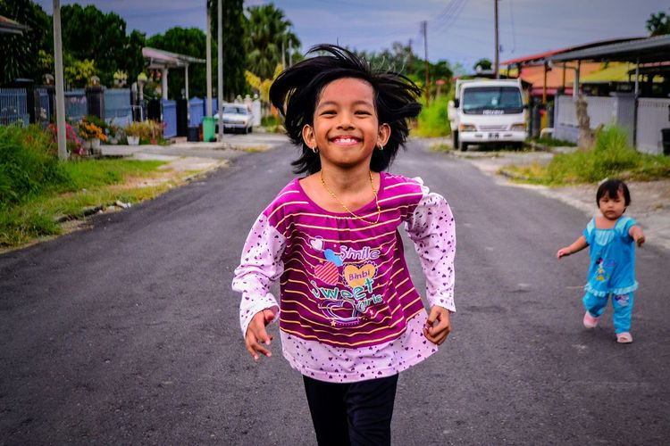 Portrait of smiling girl on road