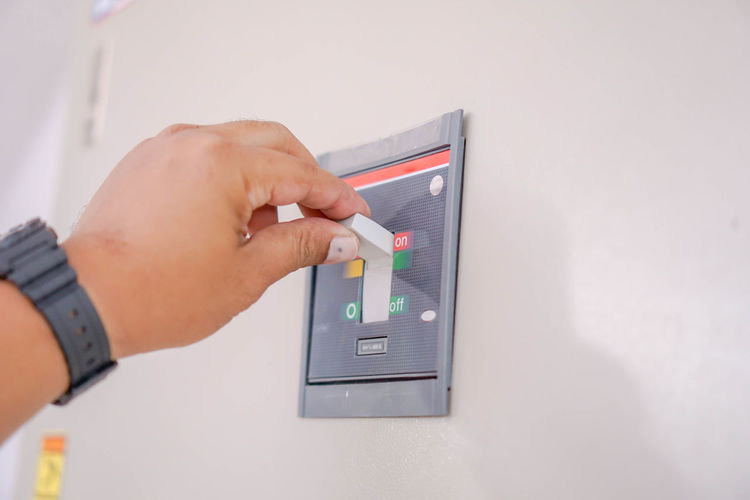 Cropped Hand Holding Switch Button