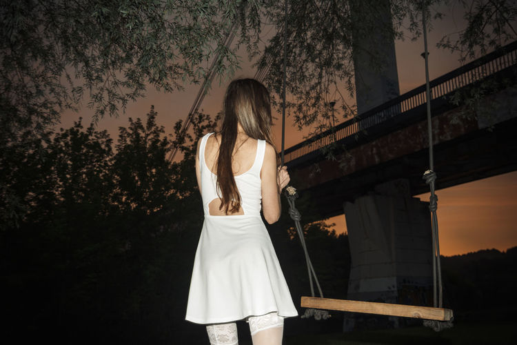 Rear view of woman standing by swing during dusk