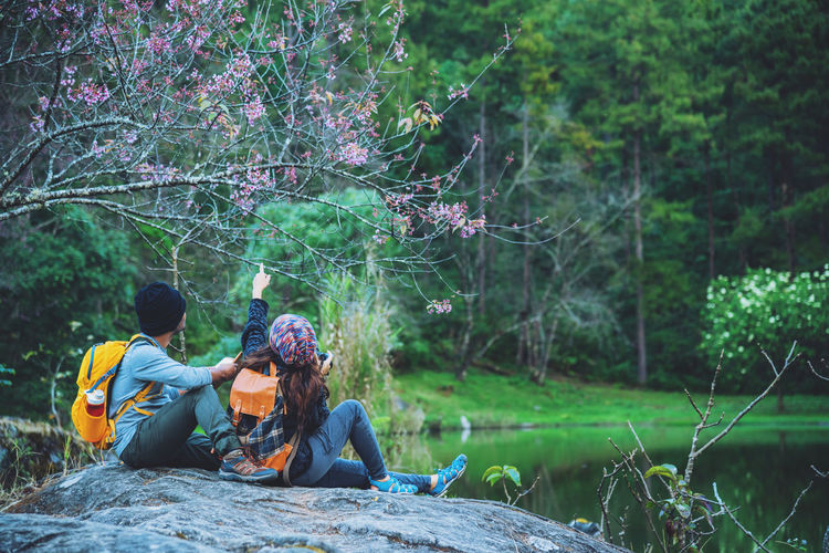 Couple sitting by lake on rock at forest