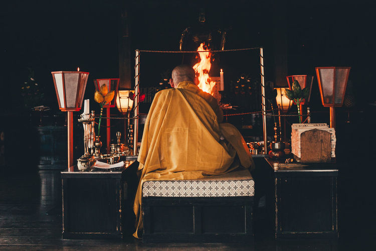 Rear view of monk praying in temple