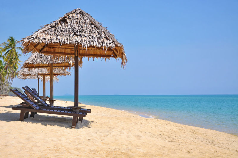 bamboo hut at the beach on sunny day Bamboo Beach Bench Blue Blue Sky Blue Water Chair Coast Coastline Holiday Hut Island Paradise Relax Rest Romantic Sea Seaside Shelter Shore Thatch Thatched Roof Vacation