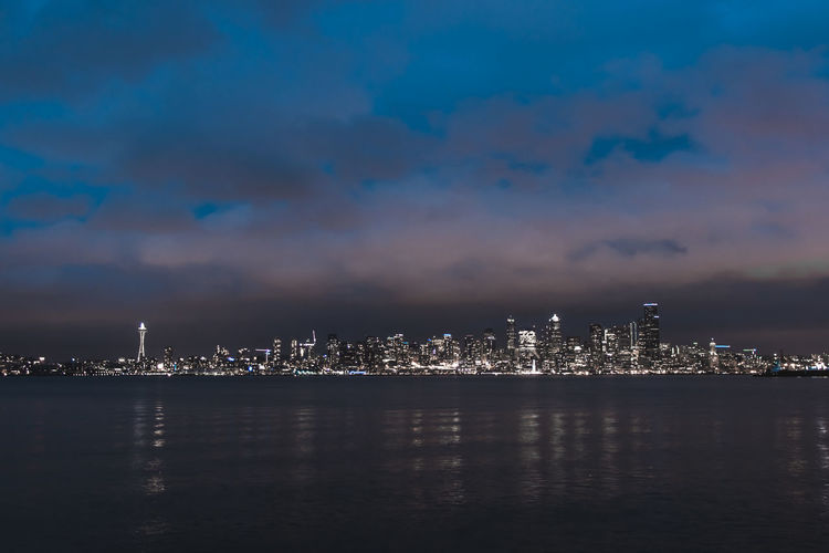 Illuminated city at waterfront against cloudy sky