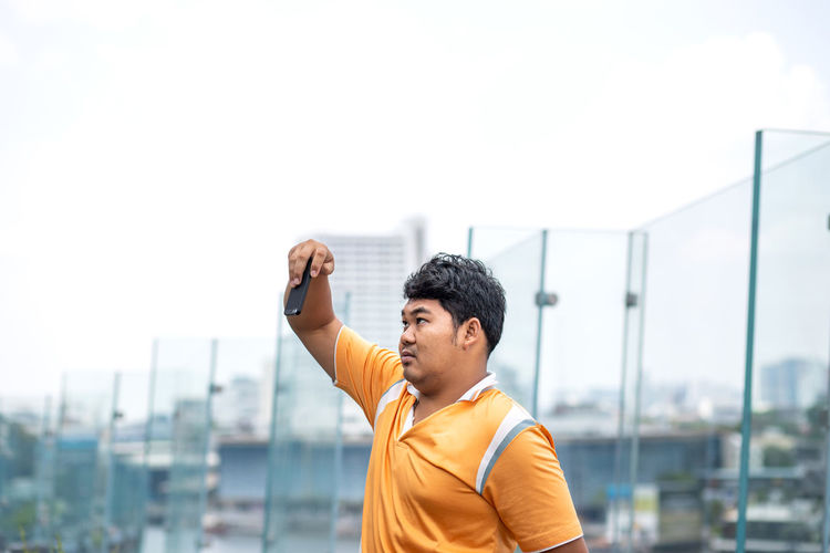 Man taking selfie against clear sky in city