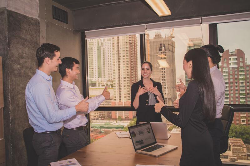 Colleagues gesturing during meeting in board room