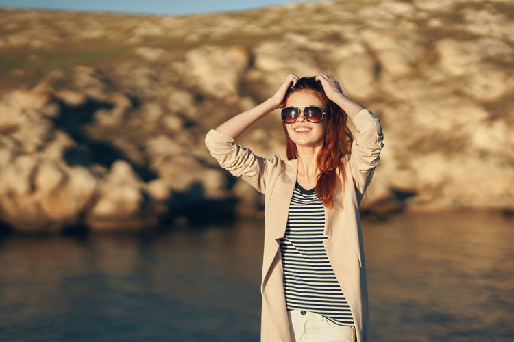 Portrait of young woman wearing sunglasses standing outdoors