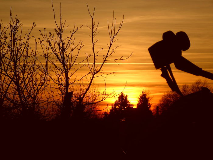 Silhouette Equipment And Bare Trees Against Orange Sky During Sunset