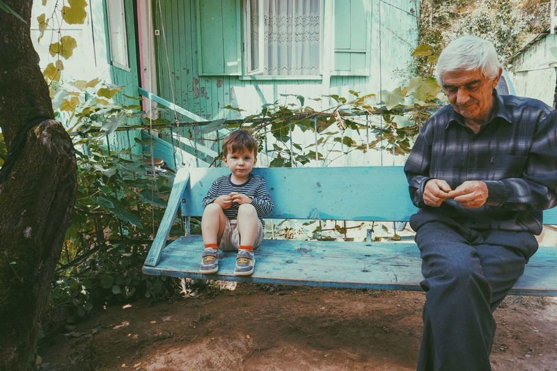 Grandfather And Grandson Sitting On Bench At Back Yard