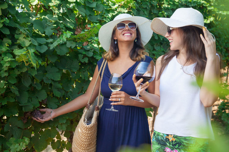 Young women drinking wine while walking by plants