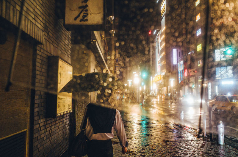 Rear View Of Woman Walking On Sidewalk Seen Through Glass In City