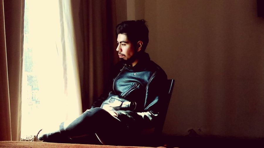 Thoughtful young man looking through window while sitting on chair at home