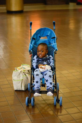 Portrait of cute toddler in baby stroller over tiled floor