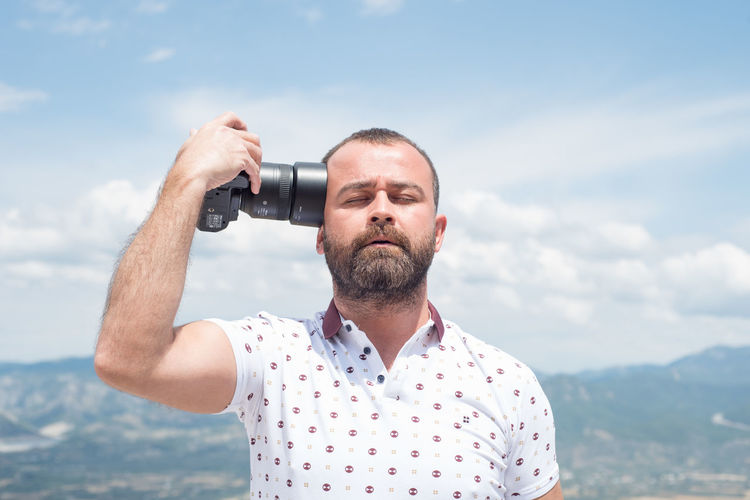 Man Holding Camera Against Sky