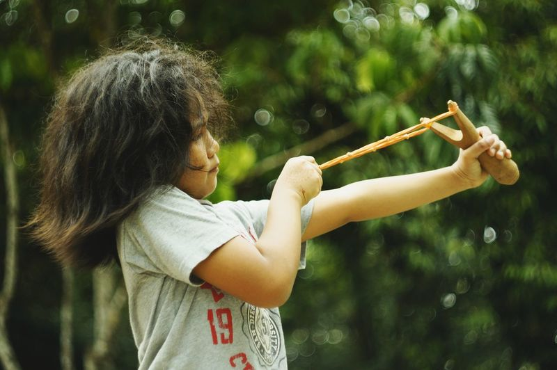 Girl aiming slingshot while standing at public park