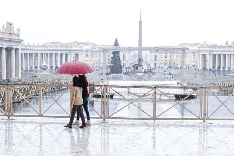 Couple walking on walkway against st peter square during rainy season