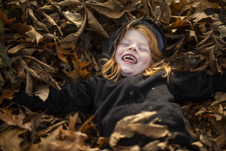 A five-year-old red head girl plays in a leaf pile. Child One Person Childhood Plant Part Leaf Emotion Lying Down Portrait Mouth Mouth Open Girls Front View Nature Happiness Land Eyes Closed  Dry Real People Outdoors Leaves Change Innocence Fall Fall Colors Girl Moments Of Happiness