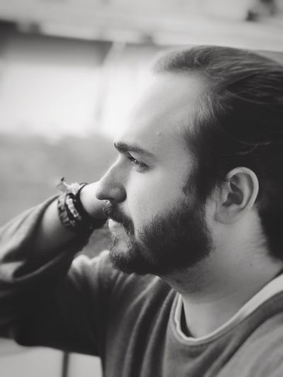 Close-up side view of young bearded man looking away