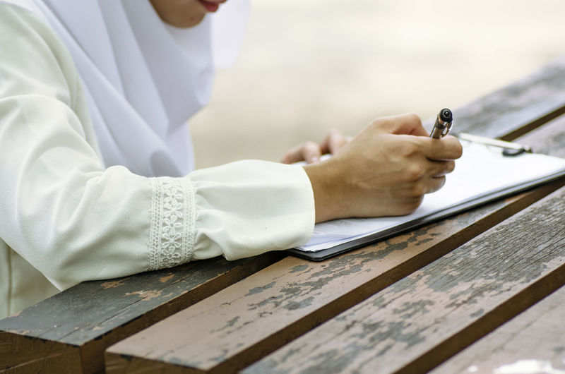 young woman signing form, sitting on wooden table Occupation Real People One Person Writing Midsection Wood - Material Healthcare And Medicine Clothing Indoors  Holding Human Hand Table Working Hand Pen Skill  Expertise Men Human Body Part Lab Coat Analyzing