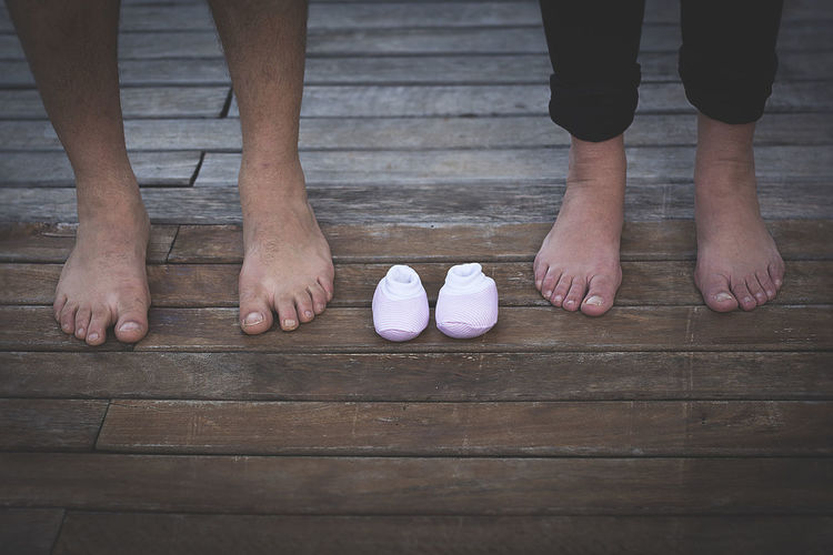 Low section of man and woman standing by baby shoes