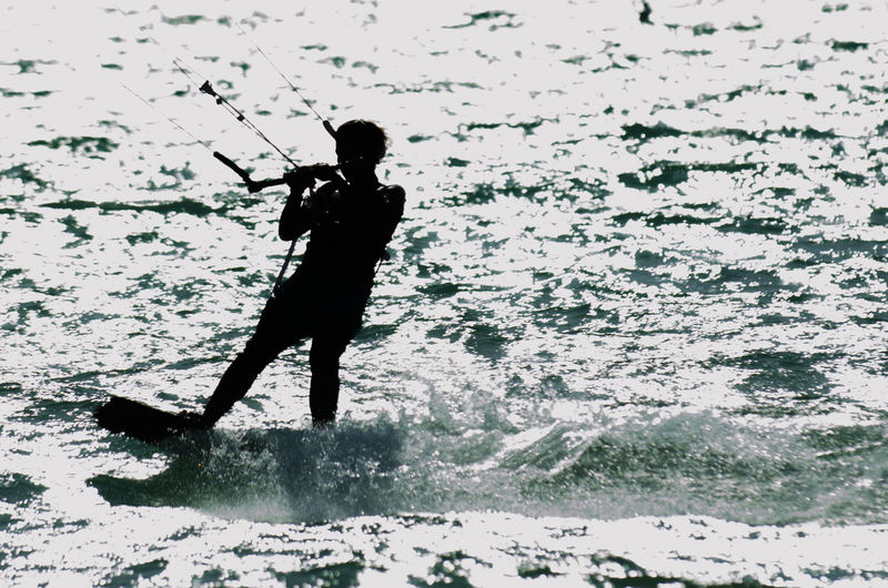 Silhouette woman doing kitesurf