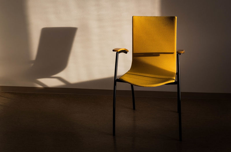 Close-up of yellow chair on table at home