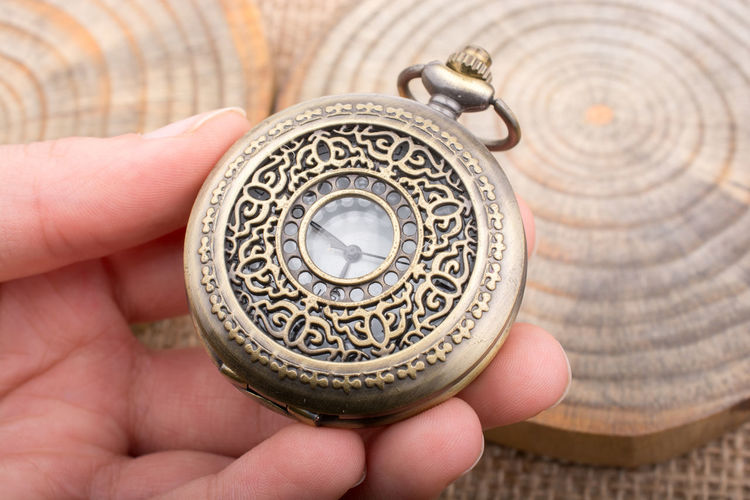 Close-up of human hand holding pocket watch on table