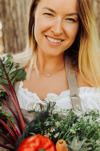 Portrait of smiling young woman holding red flowering plants