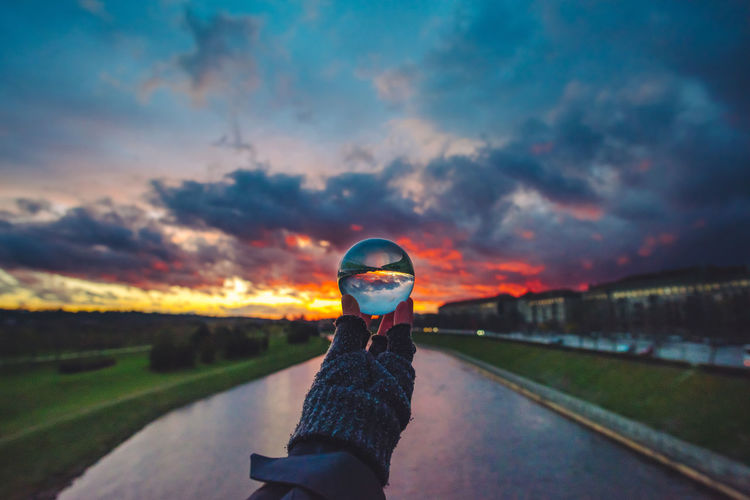 Cropped image of person holding crystal ball over river against cloudy sky