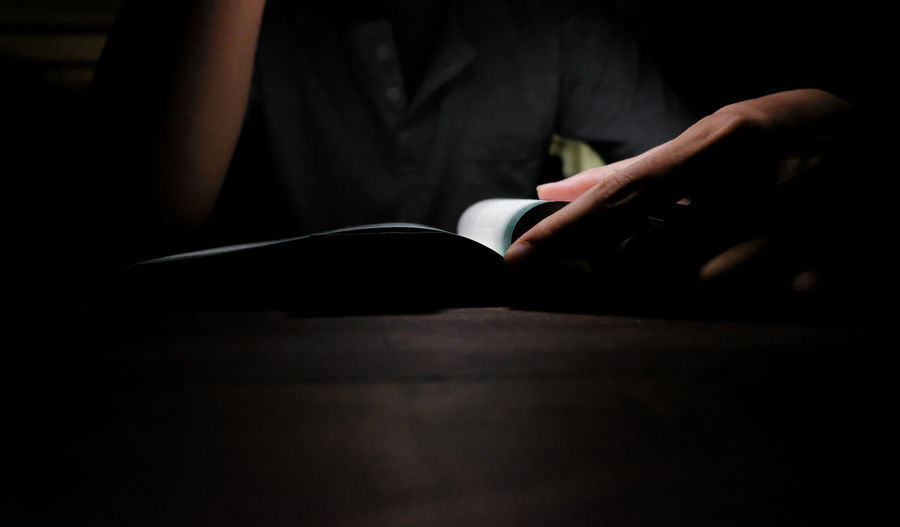 Midsection of person holding book on table at home