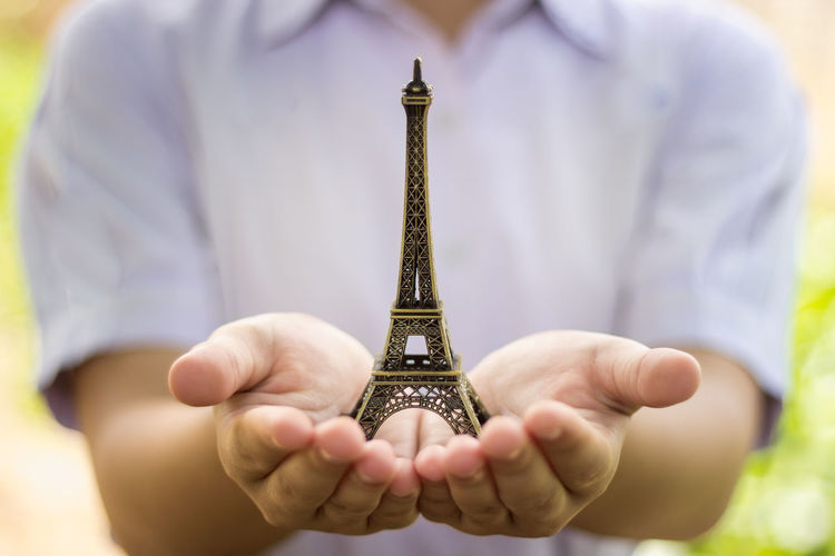 Midsection Of Woman Holding Artificial Eiffel Tower