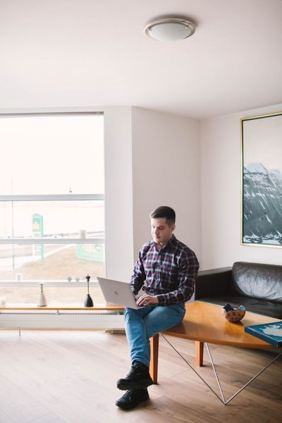 Work Working Laptop People Apartment Home Home Interior Interior Interior Design One Person Casual Clothing Full Length Sitting Real People Indoors  Front View Young Men Men Lifestyles Connection Adult Young Adult Leisure Activity Technology Wireless Technology Architecture Looking Mid Adult Going Remote Modern Hospitality