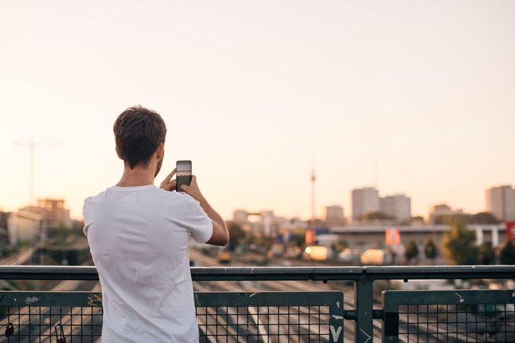 Man photographing with cityscape in background against sky