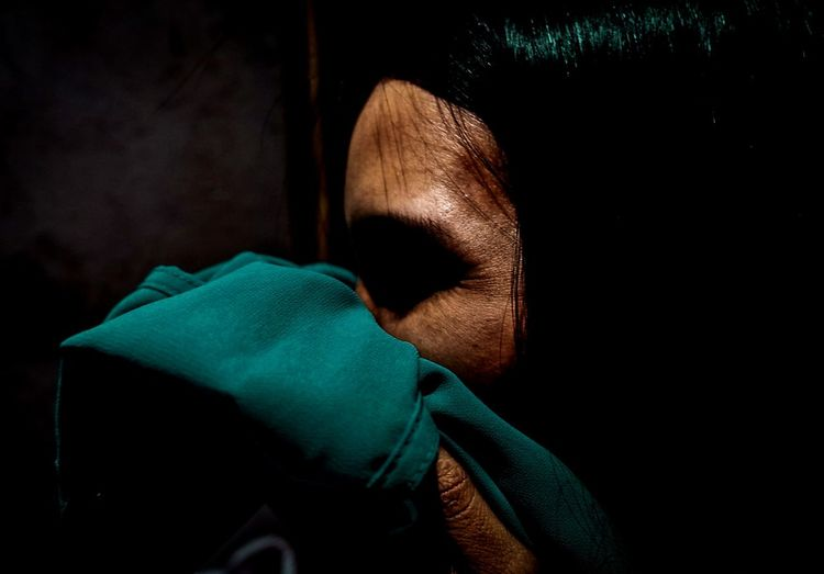 Close-up of woman covering mouth with green fabric in darkroom