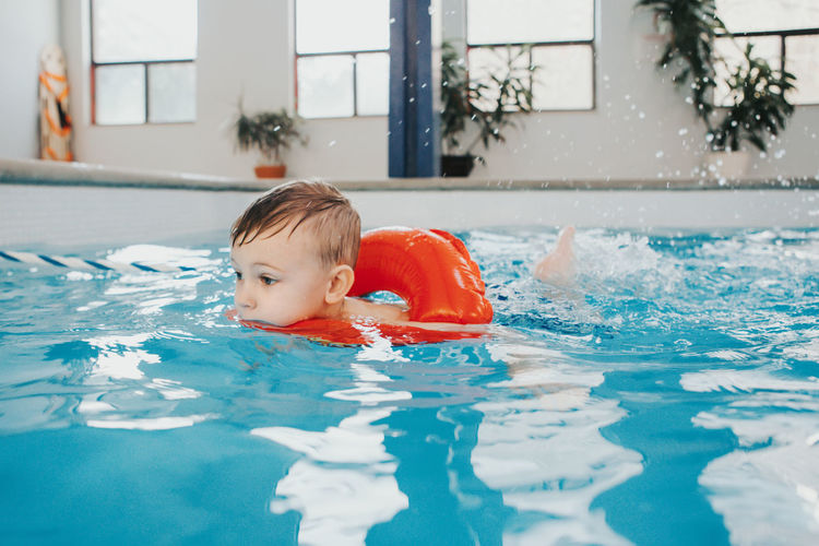 Close-up of cute boy swimming in swimming pool