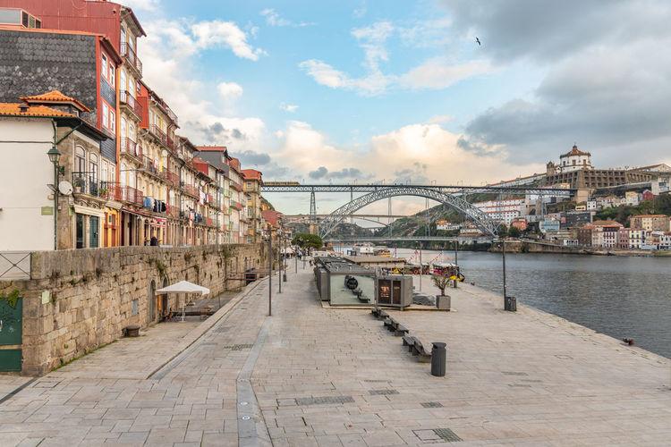 Bridge over river amidst buildings in city against sky