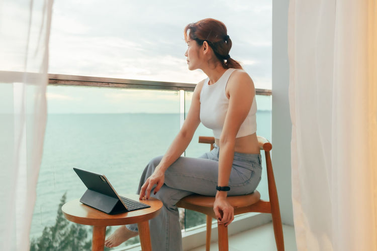 Young woman sitting on chair by sea against sky